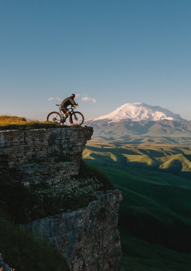 A man cycling in the mountains as part of the breathing training