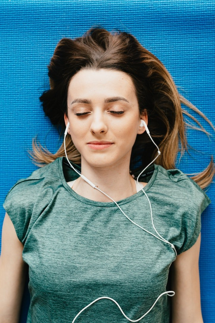 A stressed woman with earphones listening to a breathing programme online